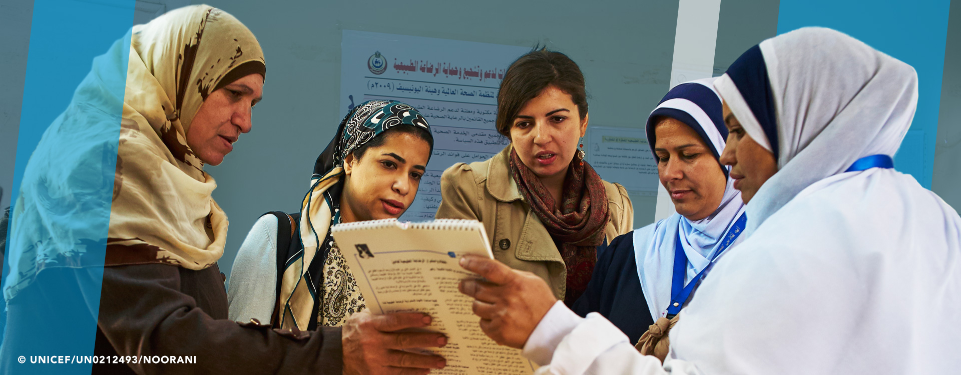 A group of women standing in a circle who appear to be a team reviewing document that they're holding in the middle of themselves. Copyright: UNICEF/UN0212493/NOORANI